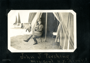 A man in a cavelry uniform sits outside a canvas tent.