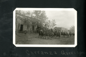 A parade of many men on horseback, four abrest, with a Mexican flag, riding through a village as a few people watch.