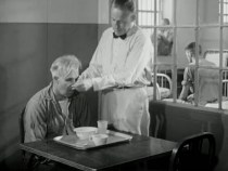 Standing, Joe feeds Mr. Rusk from a tray; Mr. Rusk is impassive.
