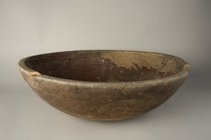 A worn and chipped wooden bowl.