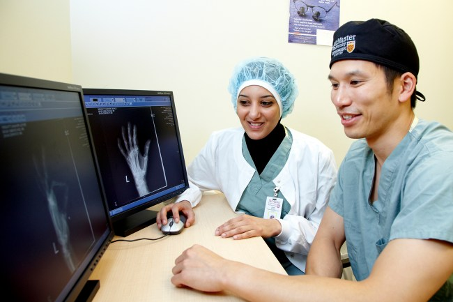 Two people in medical clothing look at monitors showing hand X-rays.
