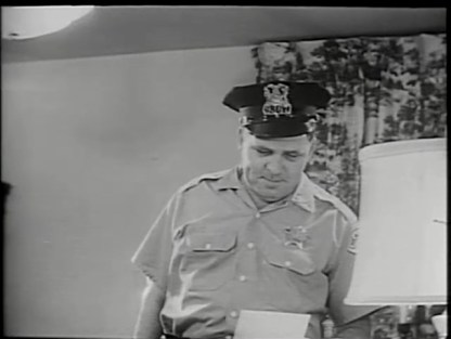 A policeman reads a suicide note.