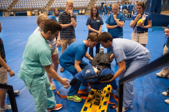 Men in scrubs lift a person onto a stability board while others watch.