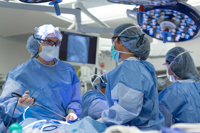 People in surgical dress working in an operating room.