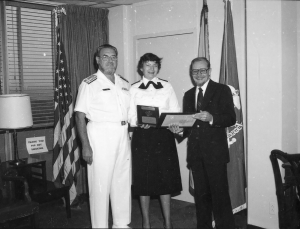 Faye Abdellah holds a plaque next to Koop, in uniform, in an office in front of flags.