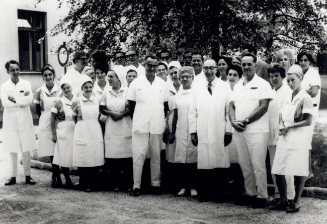 A group of people in medical clothing pose outdoors.