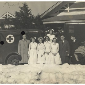 Men in suits and women in nursing uniforms stand outside in the snow in front of trucks with the red cross symbol.