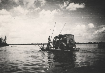 Ferrying a car accross a river on a raft.