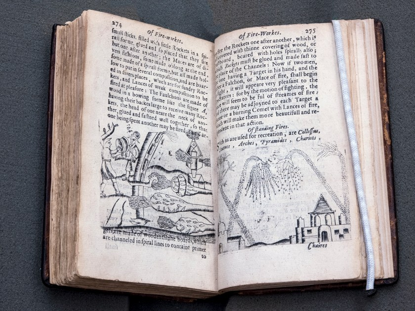 an open book with woodcuts of firworks bursting over a town and men fighting amoung various weapons augmented with fireworks.