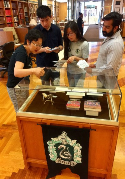 Four people looking at Harry Potter books in a glass case.