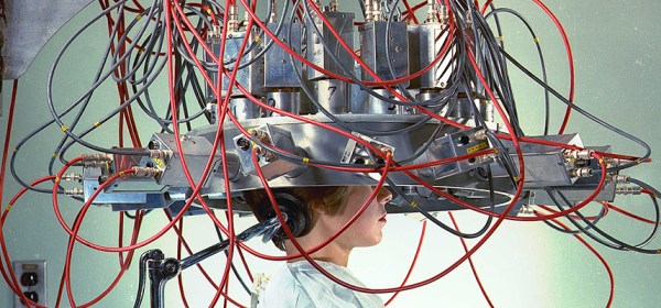 A woman sits with her head inside a complex scientific aparatus.