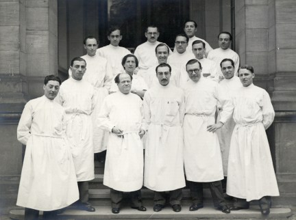 Sixteen men in white surgical coats pose on the steps of a large stone building.