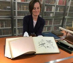 NAL staff display an open sketchbook at a drawing of birds.
