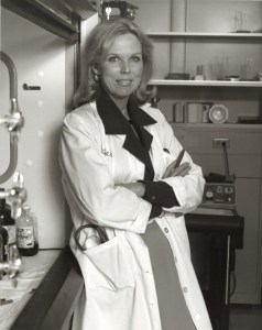 Black and white photograph of Bernadine Healy wearing a lab coat and leaning against a lab fume hood.