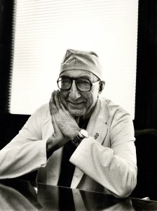 A black and white photographic portrait of DeBakey smiling, at his desk in surgeon's cap and white coat.
