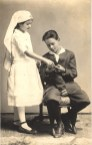 ostcard featuring a black and white photograph of a girl dressed as a Red Cross nurse assisting a blind boy knit a sock.