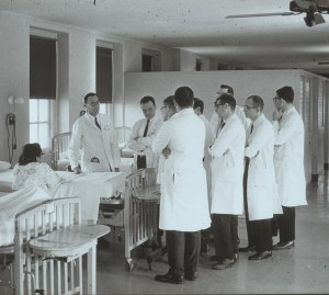 Many doctors stand near a patient during their rounds.