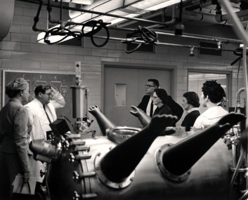 Hospital staff gather in a room with an apparatus that has long gloves into which a technician can put their hands.