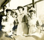 Cornelia Mercer holds an infant and poses with three nurse colleagues at the Union Protestant Infirmary in Baltimore. All are wearing white nurses uniforms. An unidentified man has his arm around another infant patient, whose hand is also being held by one of the nurses.