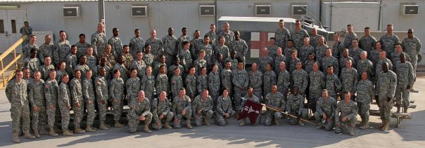 A group of 5 rows of people in camo fatigues pose with a flag and an ambulance.