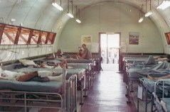 A long room of beds with bandaged patients and men in uniform at a workstation.