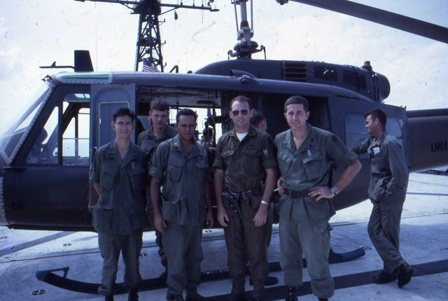 Five men in uniform stand beside a helicopter.