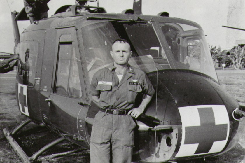 A man in uniform leans against a helicopter marked with a red cross.