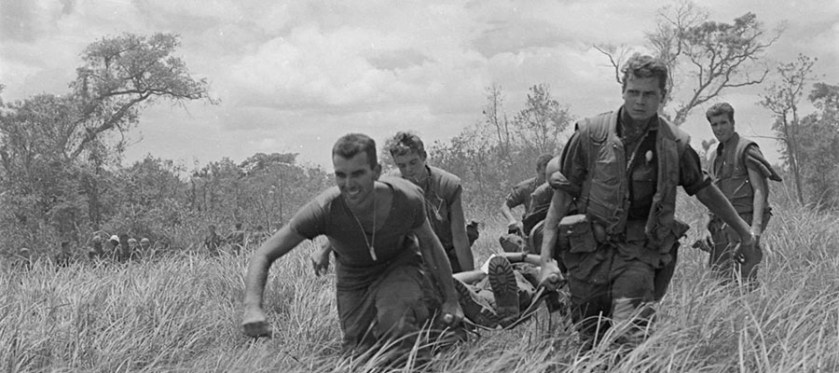Soldiers carry a wounded soldier on a stretcher though a field of high grass.