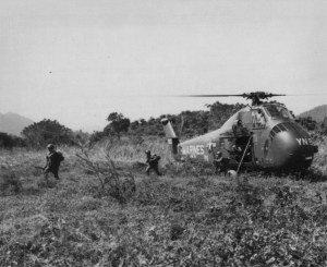 Soldiers disembark from a Marine helecopter in a field.