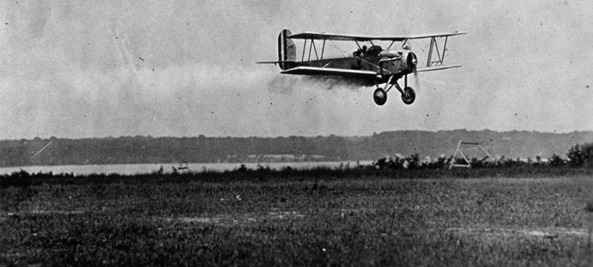 A small open biplane releases a cloud of chemical over a field.