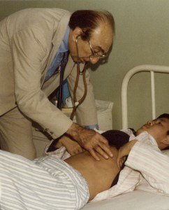 DeBakey, in a western suit, uses a stethescope to examine a patient lying on a bed.