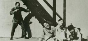 A still from a chinese black and white film shows a man pointing at three men on the ground at the foot of a staircase.