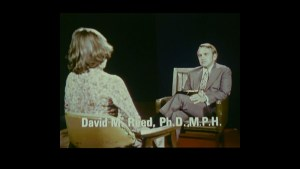 A view over a woman's shoulder of a man interviwing her in a formal setting.
