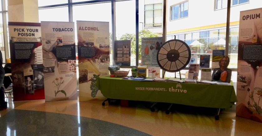 A table with giveaways and a carnival wheel, surrounded by graphic banners