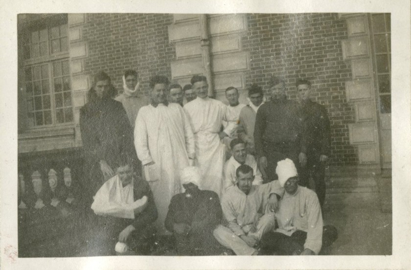 Men in bandages, men in uniform, and men in operating clothes gather on a balcony for a photograph.