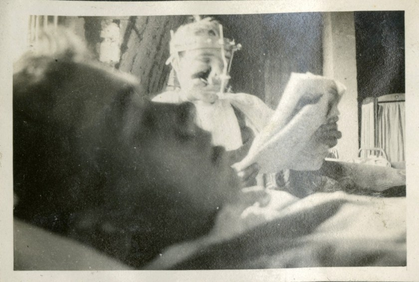 A patient in surgical headgear reads by the bedside of another patient.