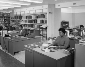 Photograph of reference librarians sitting at desks.