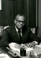 African American man (Leonidas Berry) seated at desk and looking at viewer.