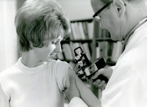 A man vaccinates a woman with an airgun.