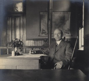 A man in a suit seated at a desk in an office with a wood stove heater..