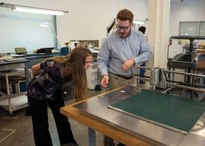 Two people look at a machine on a table with a flat surface and a moving tool on a long track on one edge.