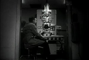 A white man in a lab coat sits at a large microscope.