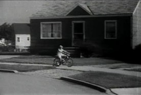 A yound white girl rides a bike in a suburban neighborhood.