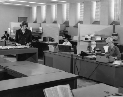 Photograph of woman standing and other staff working at their desks.