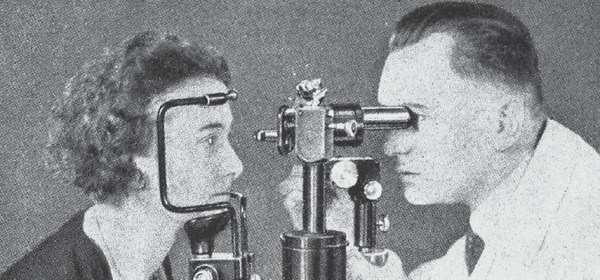 A man in a white coat uses a microscope to look into a woman's eye.