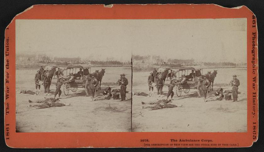 Stereograph card showing members of the Ambulance Corps carrying wounded soldiers on stretchers to the horse drawn ambulance in the field.