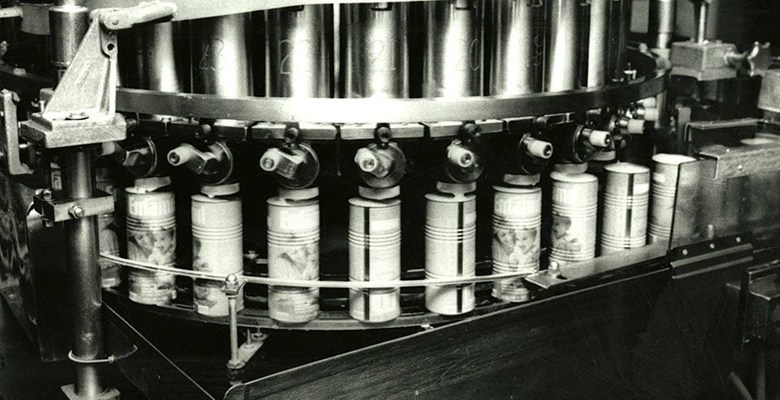 Cans of infant formula on a conveyor belt.