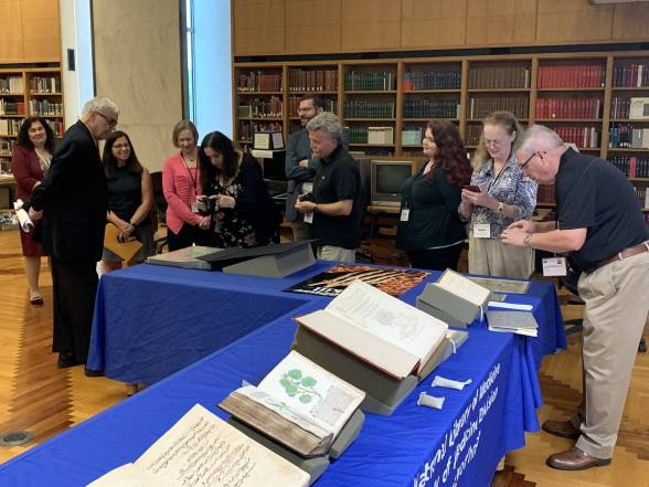 A group of people stand around a display of books on tables.
