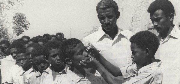 wo men, members of a trachoma control team, are observing as a young boy applies ointment to his classmates' eyes.