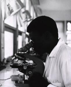 A black man inspects a specimen under a microscope